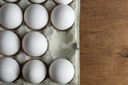 Chicken eggs are raw in the tray. The shell is white in eggs. In one section is an egg shell. On one egg lies a feather of white color. Wooden background. View from above. Close-up.