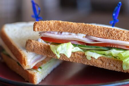 Close-up photo of a club sandwich. Sandwich with meet, prosciutto, salami, salad, vegetables, lettuce, tomato, onion and mustard on a fresh sliced rye bread on wooden background.