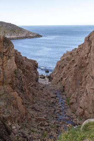 river meets ocean along a rocky shoreline with heavy water flow in a forest area, Motion river Banco de Imagens - 128595220