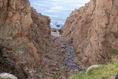 river meets ocean along a rocky shoreline with heavy water flow in a forest area, Motion river Banco de Imagens - 128586942