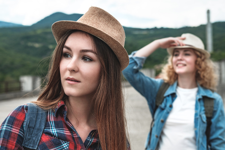 Two girls in cotton hats, tourist backpacks, denim shorts and shirts in a cage travel through modern abandoned ruins, forest and mountains go by hitchhiking Stock Photo