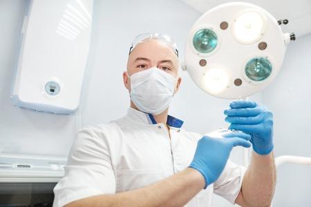 Mannelijke arts anesthesist in een badjas in een helder kantoor met een spuit met medicijnen en serieus kijken naar het frame