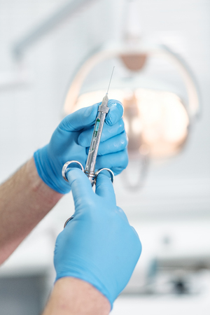 Syringe in the hands of an anesthetist in blue gloves