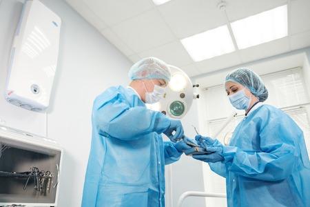 Mannelijke arts anesthesist en verpleegster in een jurk in een helder kantoor met een spuit met medicijnen en serieus kijken naar het frame Stockfoto