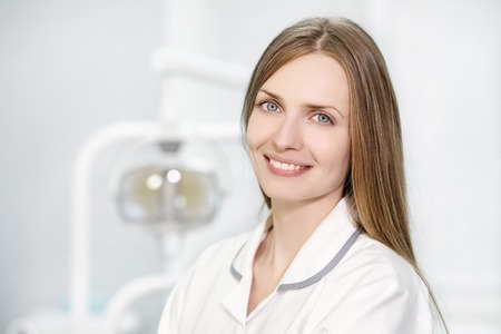 Portrait of a young beautiful woman doctor blonde in a white robe against the background of a dental chair