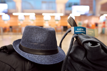 light duty: Hand luggage of backpacks and bags and a blue travelers paper hat lie on a bench at the airport, waiting for a flight on the plane