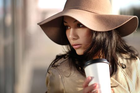 A young girl in a brown coat and hat walks out of the mall with gray and silvery packages and coffee is autumn warm and sunny.