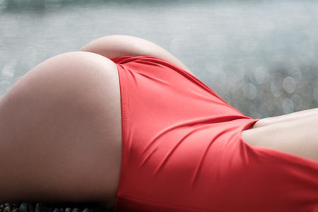 Close-up of the hips of a beautiful girl in a red bodysuit. Appetizing shape, fitness beautiful figure