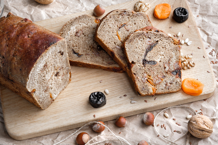 Rye bread with nuts, dried fruits, apricots and prunes, dessert. The whole loaf and the cut pieces of bread lie on brown paper on a table made of ebony. Nearby lie walnuts and hazelnuts, dried apricots and prunes. Warm key, many objects. Stock Photo