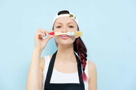 Young beautiful girl brunette painter, designer and worker paints a paint roller and brush wall. The wall is blue. Paint and brush, smile, works with satisfaction. On the model is an apron, a white tank top and a white baseball cap. Archivio Fotografico