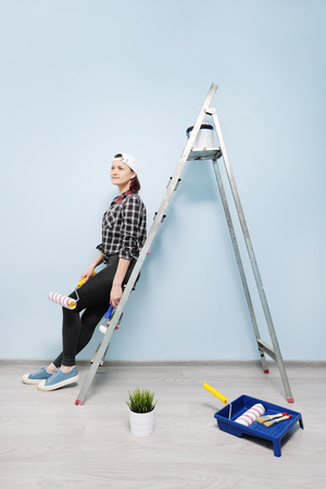 Girl working, painter in checkered shirt and white cap, sitting on the floor and looking at the blue wall. Nearby are paint tools, brushes, paint, roller. He chooses, thinks, rests, next to him goes a pet cat.