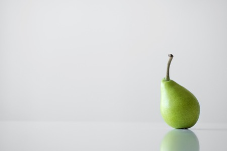 One small green yellow pear with a twig stands on a white table, a reflection, a bright light, minimalism and free space for text. A healthy and healthy diet. Imagens