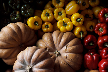Pumpkins and peppers, red, yellow and green, are on the counter in the market. Still life in dark colors from vegetables.