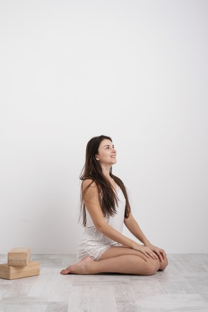 Young brunette woman in homemade pajamas doing exercises on the floor. Balances on the blocks and near the wall. White room. Foto de archivo