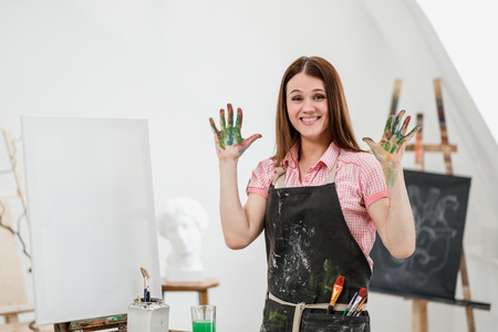 Young beautiful girl painter in a white studio with dirty palms shows class, laughs and rejoices. Art studio, drawing.