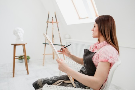 Young woman artist draws a pencil on canvas. White studio, pink shirt and apron. Drawing and painting lessons, professional artist.