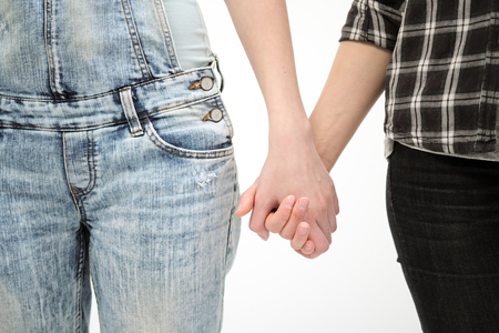 Two girls in jeans hold hands close up. White background. Homosexual gay lesbian couple. Hands in the shape of a heart.