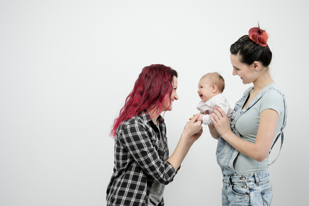 Two young women with dyed red hair and in casual clothes with a baby on a white background. Same-sex marriage and adoption, homosexual lesbian couple.