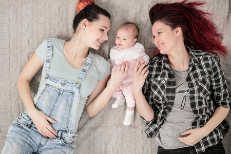 Two young women in casual clothes and with pink hair, a couple, lying on a rug with a child. Same-sex marriage, adoption.
