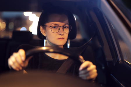Young woman with glasses at the wheel of the car. Night city and light of street lamps. Front view. Serious, focused look. He drives a car on the road, overtakes. Archivio Fotografico