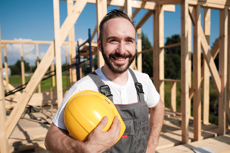 The man is a builder on the background of the roof of a frame house, in a yellow helmet and gray overalls. Stock Photo