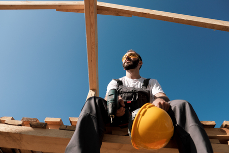 The man builder sits on the edge of the roof of the frame house, in a yellow helmet and gray overalls and a white T-shirt. The blue sky and clear sunny day.