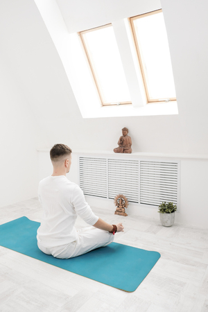 A man in white pants and bare-chested doing exercises. Yoga asanas and poses for stretching and meditating on a blue rug. Against the backdrop of a bright sport class. 版權商用圖片