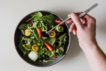A male chef decorates a salad dish in a restaurant kitchen in a black apron. White cutting board, closeup of a hand with tongs. 版權商用圖片