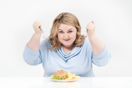 Young curvy fat woman in casual blue clothes on a white background at the table eagerly eating fast food, hamburger and french fries. Diet and proper nutrition, and harmful food.