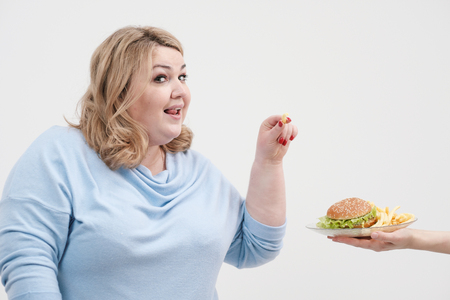 Young curvy fat woman in casual blue clothes on a white background sneaking off a plate of hamburger and french fries. Diet and proper nutrition, and harmful food. Banque d'images