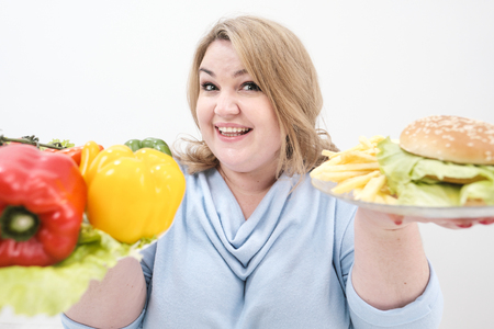 Young lush fat woman in casual blue clothes on a white background holding a vegetable salad and a plate of fast food, hamburger and fries. Diet and proper nutrition, and harmful food.