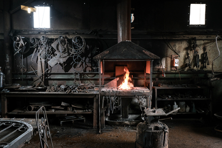 Forge, production workshop. Blacksmith tools and hot metal. The concept of manufacturing.