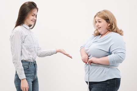 A fat woman measures her waist with a measuring tape in casual clothing on a white background. The concept of weight loss and overweight.
