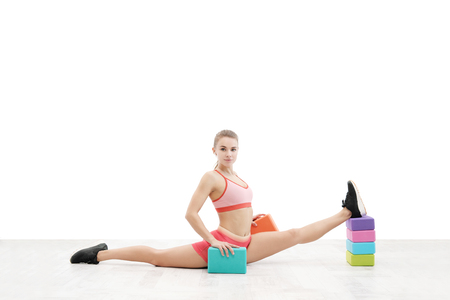 Young athletic woman with an athletic body, wearing wireless headphones and red sportswear is stretched on color blocks on a white background. Isolated concept of fitness and sport.