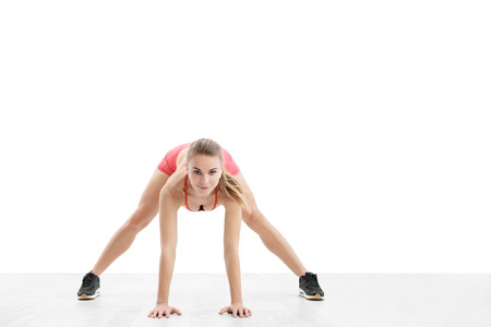 Young athletic woman with an athletic body, wearing wireless headphones and red sportswear stretched over a white background. Isolated concept of fitness and sport. Imagens