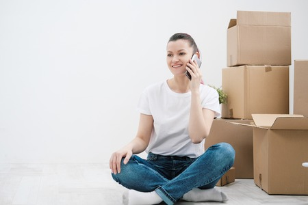 Young beautiful girl with colored hair in a white T-shirt and jeans, talking on the phone and writes messages against the background of cardboard boxes and things. The concept of transporting things on the day of moving to a new home. Stock Photo