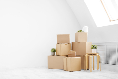 Moving to a new home. Belongings in cardboard boxes, books and green plants in pots stand on the gray floor against the background of a white wall. Concept relocation. 版權商用圖片
