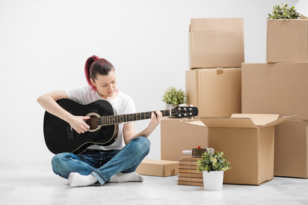 A young woman in a white T-shirt is resting and playing the guitar on the background of cardboard boxes in a new empty apartment with white walls. The concept of moving to a new home and music hobby.