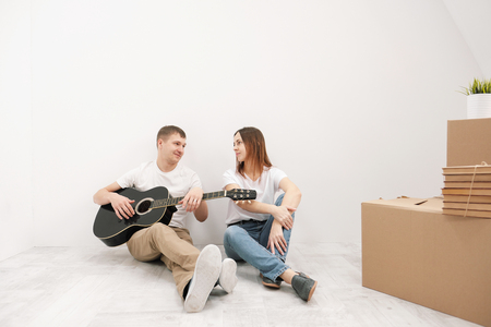 Young family, a man and a woman in white clothes in a bright room on the background of cardboard boxes and things. Topic moving to a new home. Stock Photo