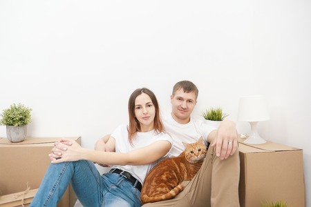 A young married couple with a red cat, a man and a woman, are sitting on the floor in a bright room against the background of cardboard boxes, green plants and things. Concept themes moving to a new home.