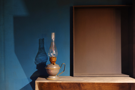 Vintage antique kerosene lamp against a dark blue wall. Wooden shelves and copy space for text.