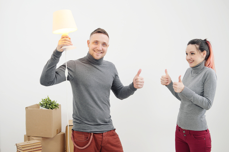 Young family, man and woman in new apartments. A man had an idea. Boxes with cargo on a white background. The concept of moving to a new home.