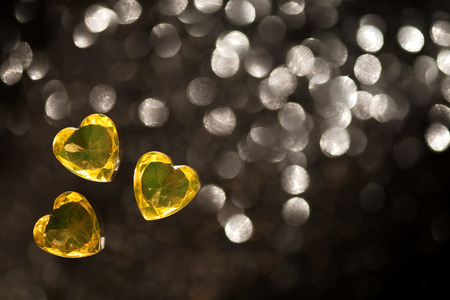 Shiny yellow, heart shape glass, jewelry, placers on a black background with blurred spots. Macro shooting close up.