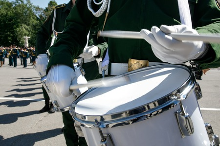 A closeup of the hands of a drummer at a military parade. White new snare drum, white sticks, green military uniform of Russia. The concept of a military parade and march. Stock Photo
