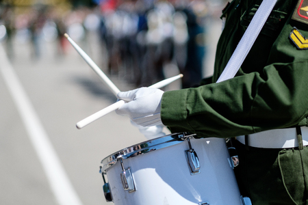 A closeup of the hands of a drummer at a military parade. White new snare drum, white sticks, green military uniform of Russia. The concept of a military parade and march. Stockfoto