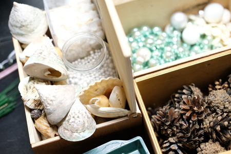 Dried flowers, cones and acorns in a wooden box on florist decorator's ftole. The concept of creating Christmas wreaths and decor. Stock Photo