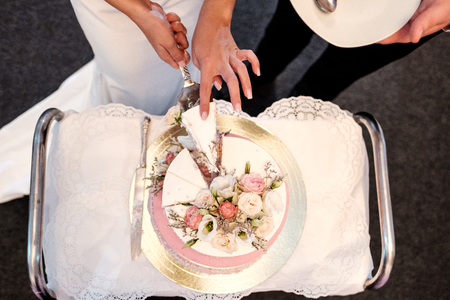 The newlyweds, the bride and groom, cut the wedding cake at the banquet. The concept of organizing a wedding and decoration of the celebration.