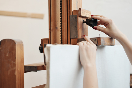 Woman artist fastens a canvas on a large wooden easel. The concept of the artist.