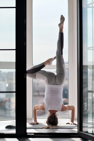 Young beautiful athletic woman blonde in white sportswear doing yoga and stretching on the balcony at home. Performs headstand. Concept of home sport and active lifestyle.