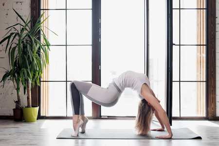 Young beautiful athletic woman blonde in white sportswear doing yoga and stretching on a gray rug on the background of large window of multi-storey building. Home sport and active lifestyle concept.
